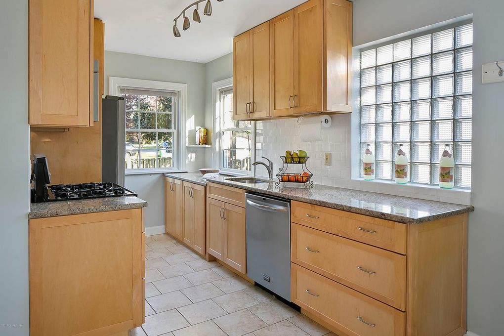 Louisville Kentucky Home Staging, Galley Kitchen, Granite Countertops, Tile Flooring, Stainless and Black Gas Range, Stainless Steel Appliances, Subway Tile, Chrome Fixtures, Glass Block Window