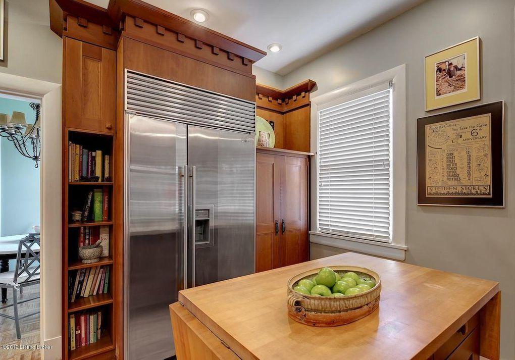 craftsman-style kitchen cabinets, sub-zero refrigerator, dental molding, butcherblock island, built-in bookshelves