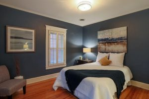 bedroom with furniture, hardwood floors, linavy wall paint, plantation shutters, white comforter, bedside table, bedside lighting, navy throw, art over bed