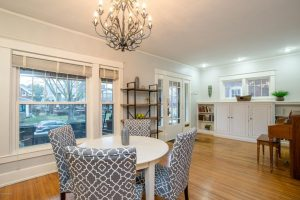 dining room table, dining room chairs, shelving unit, hardwood floors, light gray wall paint, built in cabinets