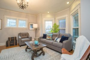 staged family room, light grey wall paint, grey rug, grey sofa, plant, coffee table, standing lamp, leather chair, windows